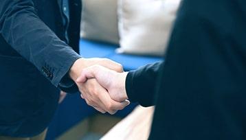 国内外の事業パートナーと握手を交わす様子